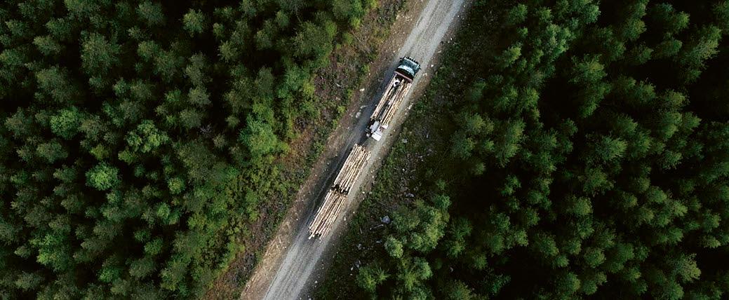 Drönarbild på timmerbil på väg genom skogslandskap