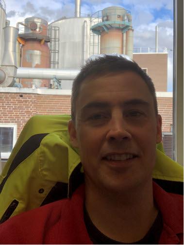 Magnus i sin kontorsstol med Hallsta pappersbruk i bakgrunden