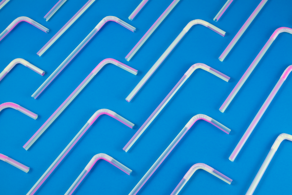 Plastic straws evenly placed on a blue background