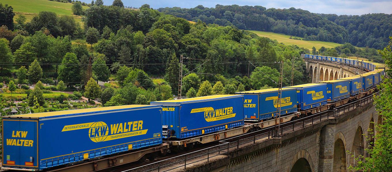 En blå lastbil från LKW WALTER på en sommarväg