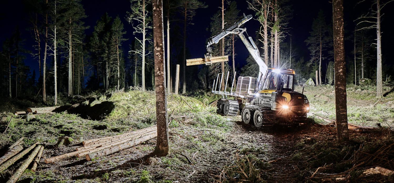 En skotare jobbar natt och  transporterar ut skördat virke ur skogen.