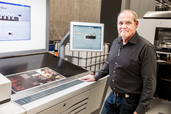 Wil Pfeiffer standing beside printing press