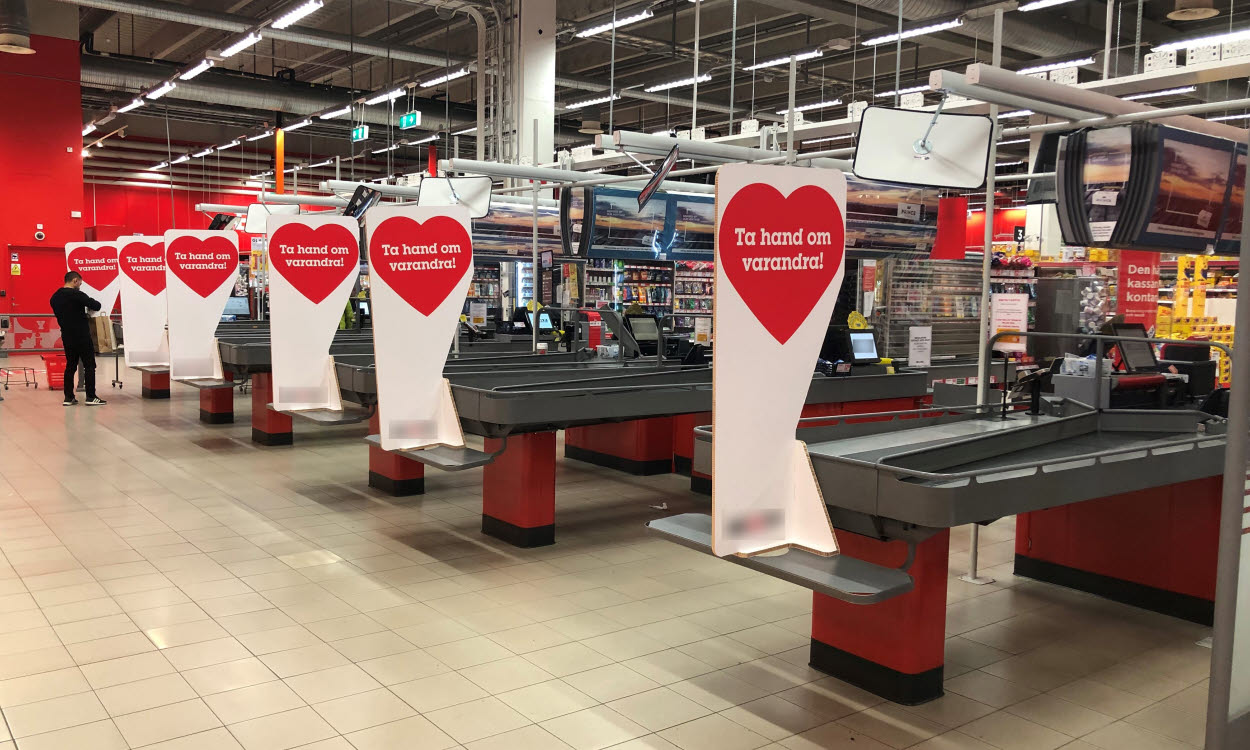 Physical paperboard barriers between shoppers at Swedish grocery stores