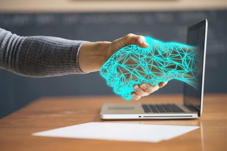 Människa skakar hand med virtuell person i datorn