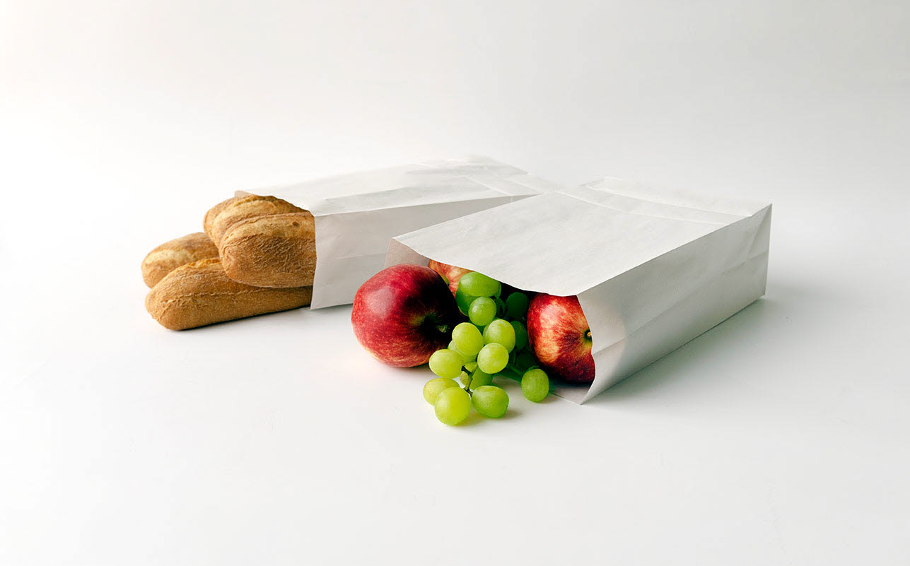 Bread and fruit in white paper bags