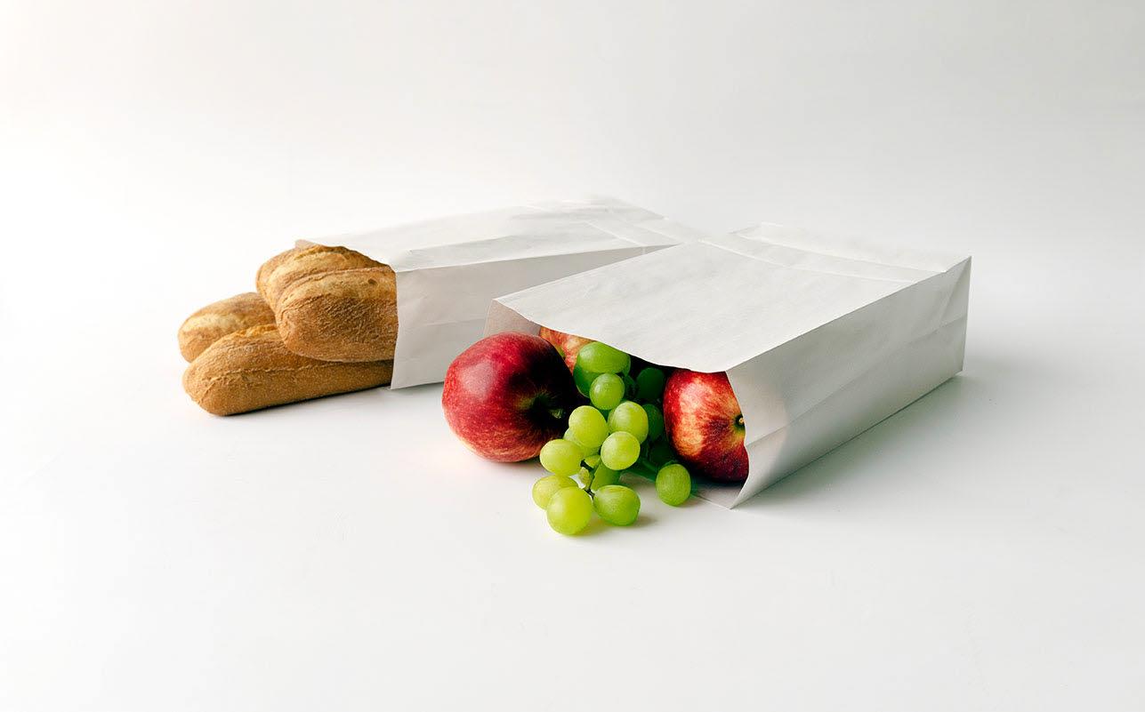 Bröd och frukt i vita papperspåsar