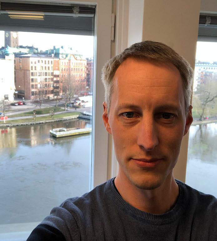 Markus framför ett fönster med vatten i bakgrunden